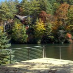 patio with steel cable railing overlooking a lake and trees
