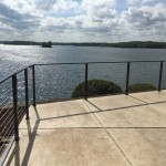 patio with steel cable railing overlooking a large lake