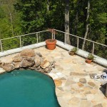 inground pool surrounded by a protective steel cable railing fence