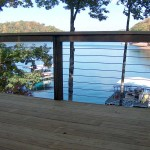 outdoor deck with steel cable railing overlooking a lake and trees
