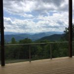 outdoor deck with steel cable railing overlooking trees and mountains