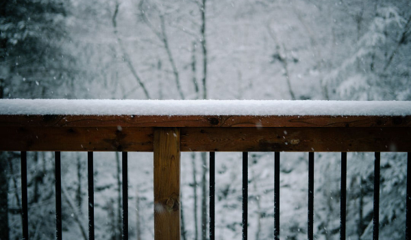 snow piled up on a deck fence beam