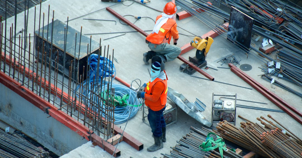 two construction workers surrounded by steel pipes and bars